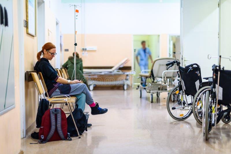 Υπομονετική συνεδρίαση στη αίθουσα αναμονής διαδρόμων θαλάμων νοσοκομείων με IV στοκ εικόνα με δικαίωμα ελεύθερης χρήσης