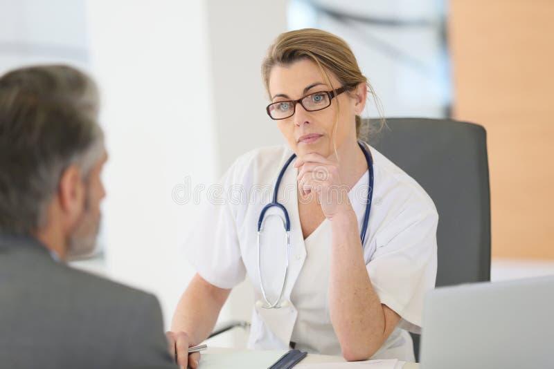 Υπομονετικός ειδικός γιατρών συνεδρίασης στοκ εικόνα με δικαίωμα ελεύθερης χρήσης