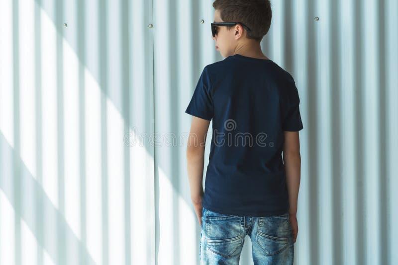 υποστηρίξτε την όψη Το νέο αγόρι hipster που ντύνεται στη μαύρη μπλούζα είναι στάσεις εσωτερικές ενάντια στον άσπρο τοίχο Χλεύη ε στοκ φωτογραφία με δικαίωμα ελεύθερης χρήσης