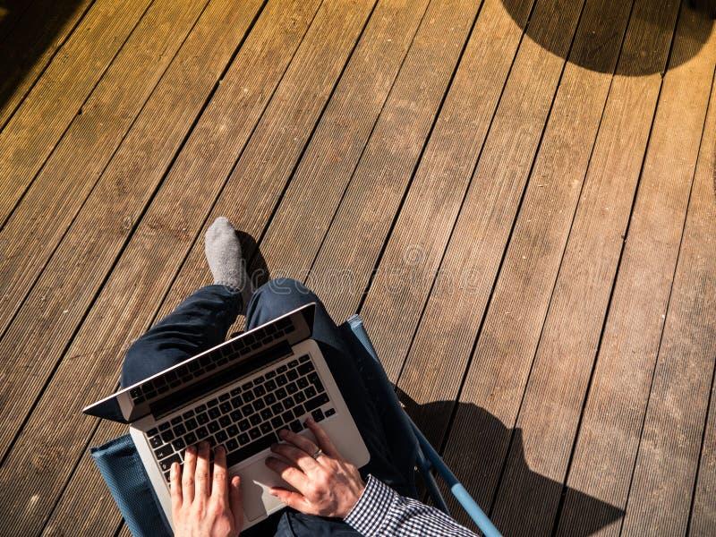 Υπουργείο Εσωτερικών: Νεαρός άνδρας που εργάζεται με το lap-top του στοκ εικόνα
