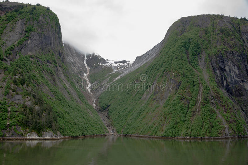 Υποχωρώντας παγετώνας μεταξύ δύο απότομων βουνών στο φιορδ βραχιόνων της Tracy, Αλάσκα στοκ εικόνα με δικαίωμα ελεύθερης χρήσης