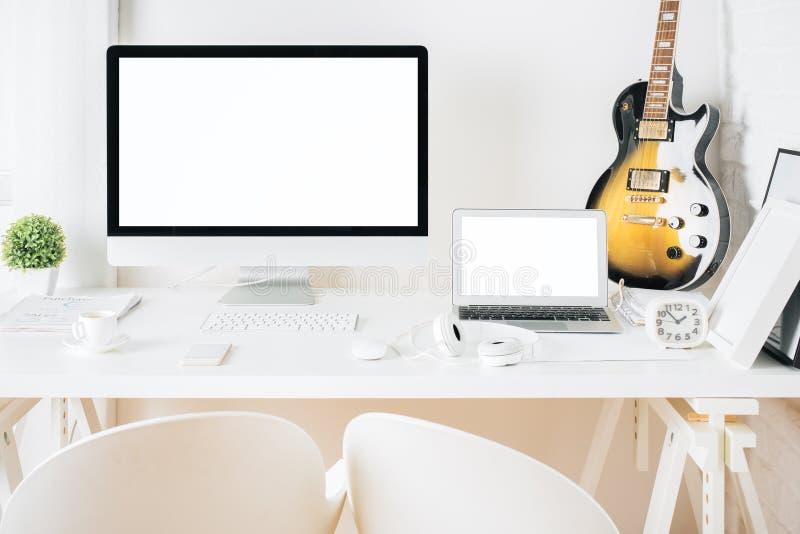 Υπολογιστής γραφείου με τις κενές συσκευές και την κιθάρα στοκ φωτογραφία
