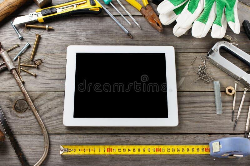 Υπολογιστής ταμπλετών με μια κενή οθόνη με τα παλαιά εργαλεία στοκ φωτογραφία