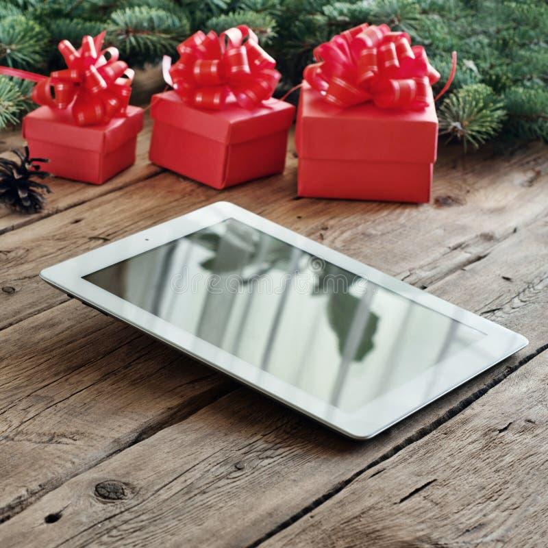 Download Υπολογιστής ταμπλετών με τα δώρα Χριστουγέννων στην ξύλινη επιτραπέζια κινηματογράφηση σε πρώτο πλάνο Στοκ Εικόνα - εικόνα από ημέρα, κάρτα: 62714173