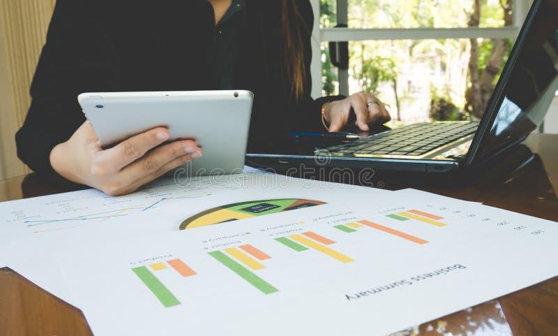 Υπολογιστής χρήσης εργαζόμενων γυναικών και εργασία tabletfor με την επιχειρησιακή περίληψη ή έκθεση επιχειρηματικών σχεδίων με τ στοκ εικόνες