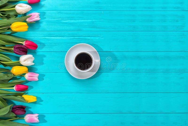 Υπόβαθρο άνοιξη! Ζωηρόχρωμες τουλίπες ανθοδεσμών και ένα φλιτζάνι του καφέ στο μπλε υπόβαθρο Ευχετήρια κάρτα διακοπών για την ημέ στοκ εικόνα