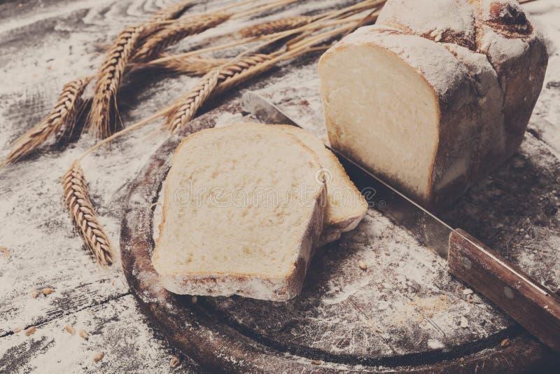 Υπόβαθρο έννοιας αρτοποιείων Τεμαχισμένα φρυγανιά ψωμί και μαχαίρι στοκ εικόνες