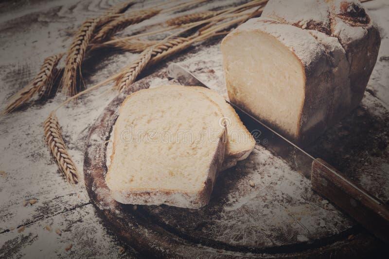 Υπόβαθρο έννοιας αρτοποιείων Τεμαχισμένα φρυγανιά ψωμί και μαχαίρι στοκ φωτογραφίες