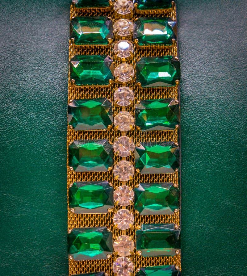 Υπόβαθρο δέρματος με τους πράσινους πολύτιμους λίθους στοκ εικόνα