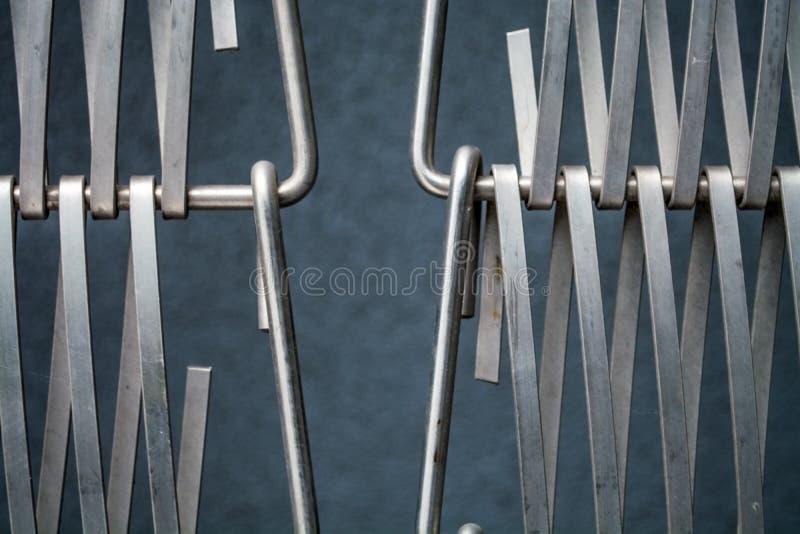 Υπόβαθρο ή σύσταση σε έναν γκρίζο τοίχο ένα δικτυωτό πλέγμα από το μέταλλο ένα καλώδιο που συνδυάζει μεταξύ τους Γάντζοι και βρόχ στοκ φωτογραφίες