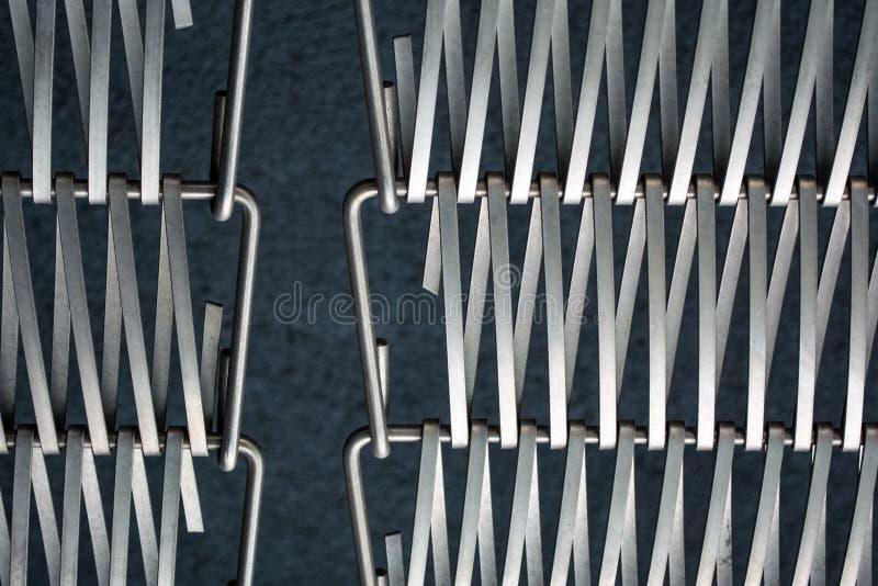 Υπόβαθρο ή σύσταση σε έναν γκρίζο τοίχο ένα δικτυωτό πλέγμα από το μέταλλο ένα καλώδιο που συνδυάζει μεταξύ τους Γάντζοι και βρόχ στοκ φωτογραφία με δικαίωμα ελεύθερης χρήσης