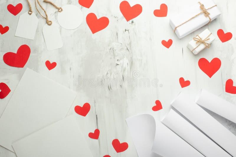 Υπόβαθρο βαλεντίνων με τις κόκκινες καρδιές, τα δώρα, και τις άσπρες κάρτες για το σχέδιο σε ένα άσπρο υπόβαθρο Ευτυχής χλεύη καρ στοκ φωτογραφίες