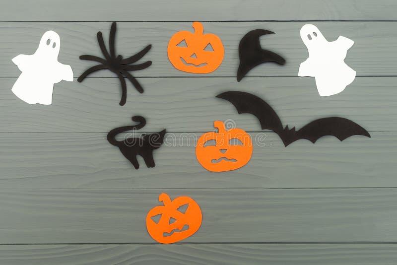 Υπόβαθρο διακοπών αποκριών με τρεις κολοκύθες, τη γάτα, την αράχνη, το ρόπαλο, καπέλο και δύο φαντάσματα στοκ φωτογραφία