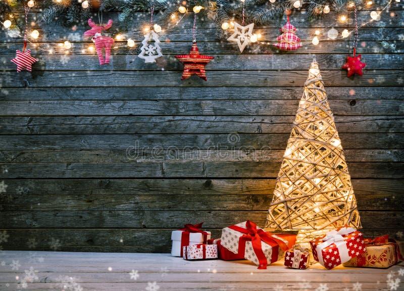 Υπόβαθρο διακοπών με το φωτισμένα χριστουγεννιάτικο δέντρο, τα δώρα και το δ στοκ εικόνες