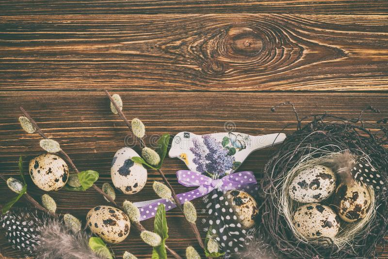 Υπόβαθρο διακοπών Πάσχας, κάρτα - αυγά Πάσχας σε μια φωλιά με τους κλάδους άνοιξη της ιτιάς και ντεκόρ στοκ φωτογραφία με δικαίωμα ελεύθερης χρήσης