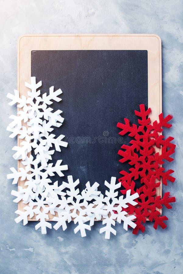 Υπόβαθρο διακοπών Χριστουγέννων με τον κενό πίνακα κιμωλίας Τοπ όψη Ζωηρόχρωμα snowflakes στο μαύρο πίνακα με το διάστημα αντιγρά στοκ φωτογραφία με δικαίωμα ελεύθερης χρήσης