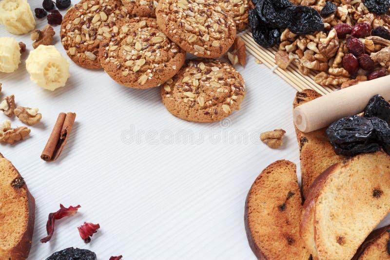 Υπόβαθρο εγχώριων αρτοποιείων με τα μπισκότα, τα ξύλα καρυδιάς, τα δαμάσκηνα και τις σταφίδες στοκ εικόνα με δικαίωμα ελεύθερης χρήσης