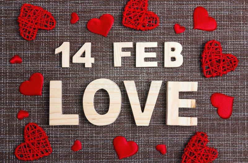 Υπόβαθρο ημέρας βαλεντίνου με την επιγραφή και κόκκινες καρδιές sackcloth στοκ φωτογραφία με δικαίωμα ελεύθερης χρήσης