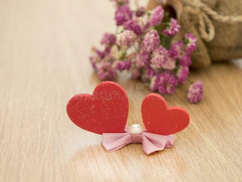 Υπόβαθρο ημέρας βαλεντίνων με τις κόκκινες καρδιές στο ξύλινο πάτωμα και τα θολωμένα ρόδινα τριαντάφυλλα στο υπόβαθρο άνδρας αγάπ στοκ φωτογραφία με δικαίωμα ελεύθερης χρήσης
