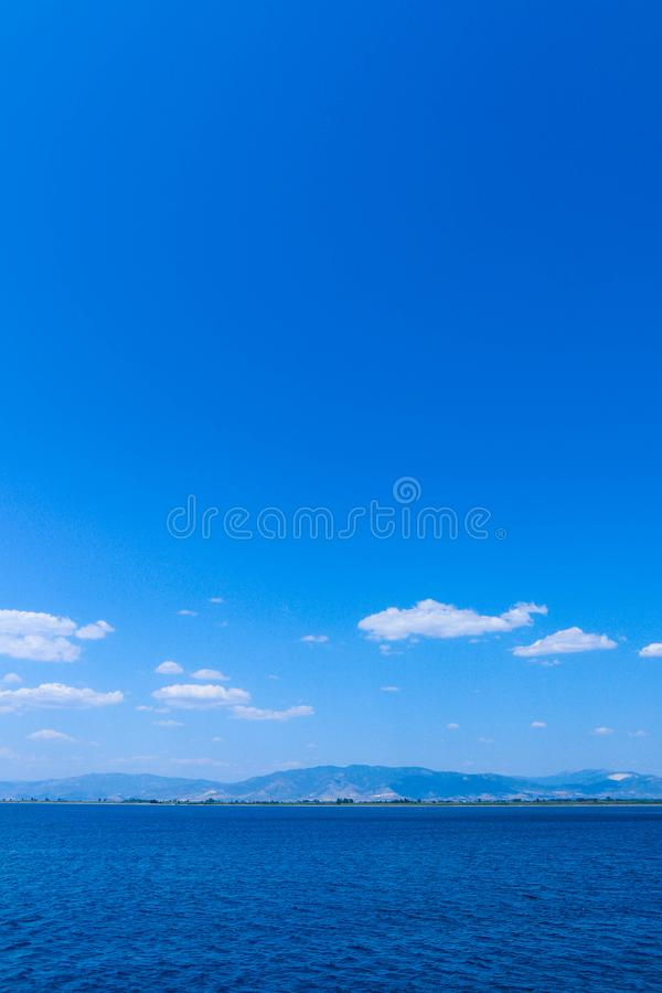 Υπόβαθρο θαλάσσιου νερού, ομιχλώδη βουνά, σκηνικό Μπλε ωκεάνια ηρεμία στοκ εικόνα