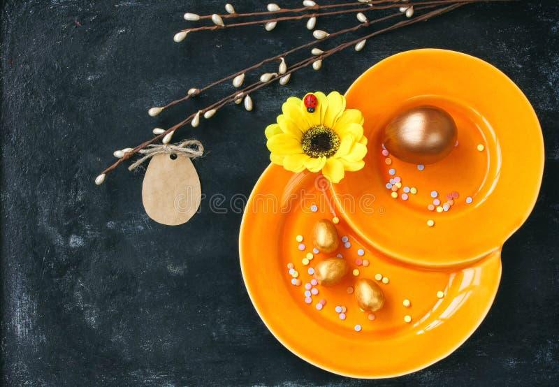 Υπόβαθρο διακοπών Πάσχας, πορτοκαλί πιάτο, χρυσά αυγά, ετικέττα εγγράφου στοκ φωτογραφία με δικαίωμα ελεύθερης χρήσης