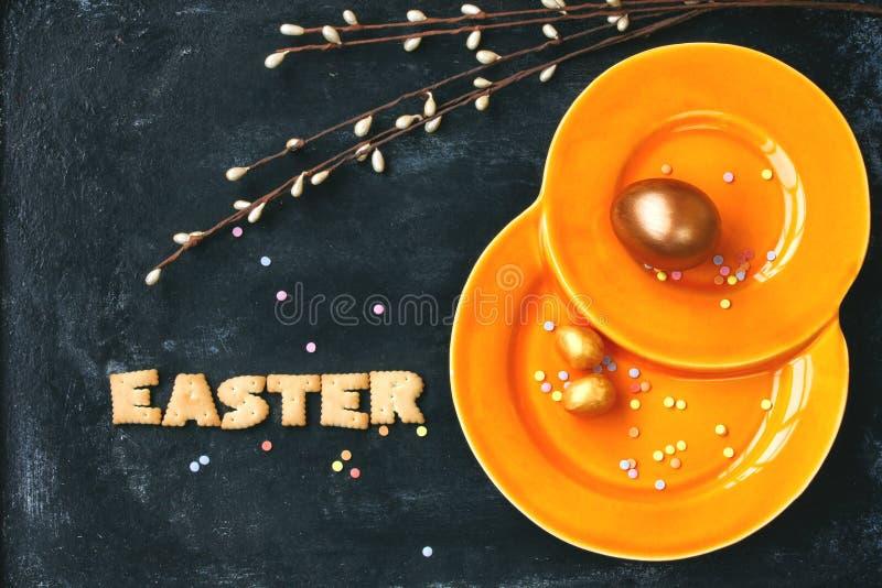 Υπόβαθρο διακοπών Πάσχας, πορτοκαλί πιάτο, χρυσά αυγά στοκ εικόνες με δικαίωμα ελεύθερης χρήσης
