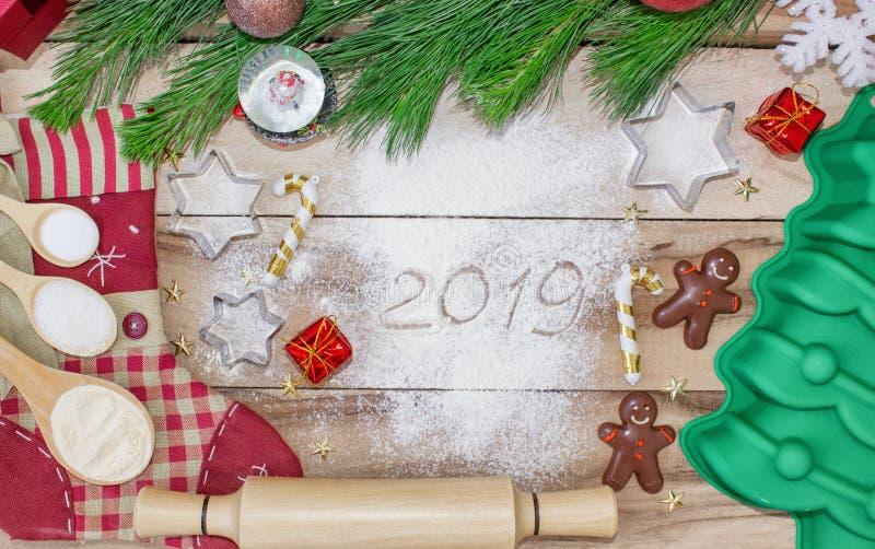 Υπόβαθρο κέικ ψησίματος Χριστουγέννων Η επιγραφή στο αλεύρι -2019 Συστατικά και εργαλεία foedients και εργαλεία για το ψήσιμο - α στοκ εικόνες