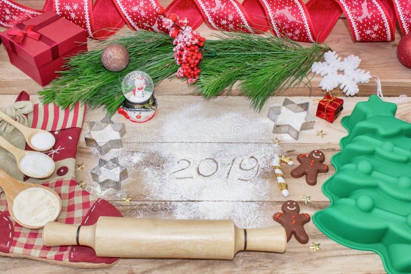 Υπόβαθρο κέικ ψησίματος Χριστουγέννων Η επιγραφή στο αλεύρι -2019 Συστατικά και εργαλεία foedients και εργαλεία για το ψήσιμο - α στοκ φωτογραφία με δικαίωμα ελεύθερης χρήσης