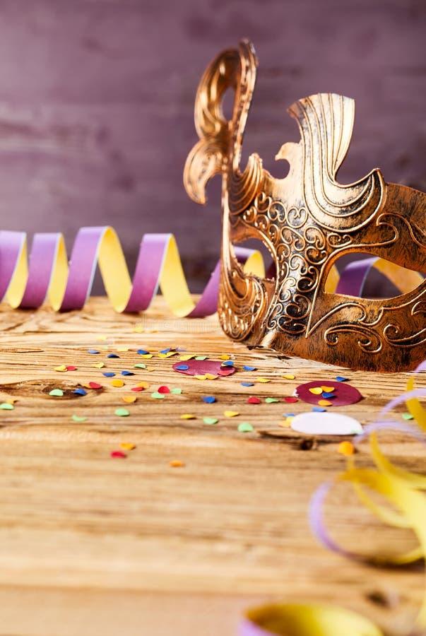 Υπόβαθρο καρναβαλιού με τη χρυσή μάσκα στοκ εικόνες