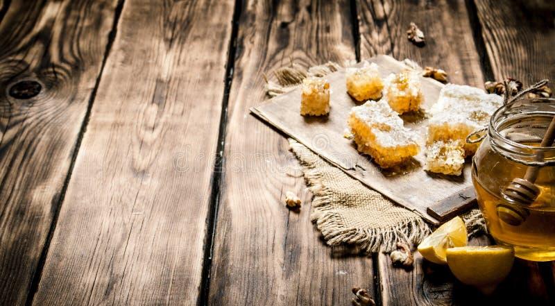 Υπόβαθρο μελιού Φυσικά φέτες και ξύλα καρυδιάς λεμονιών μελιού στοκ εικόνες