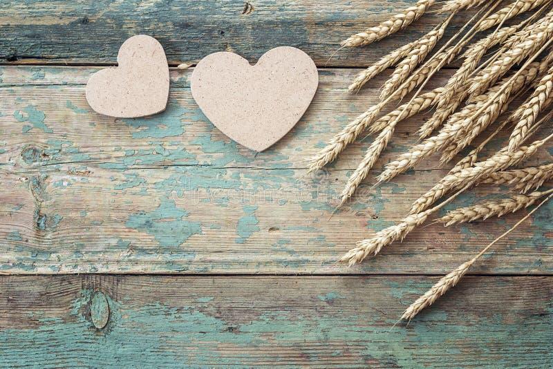 Υπόβαθρο με τα αυτιά του σίτου και των ξύλινων καρδιών στον παλαιό μπλε κάπρο στοκ εικόνα