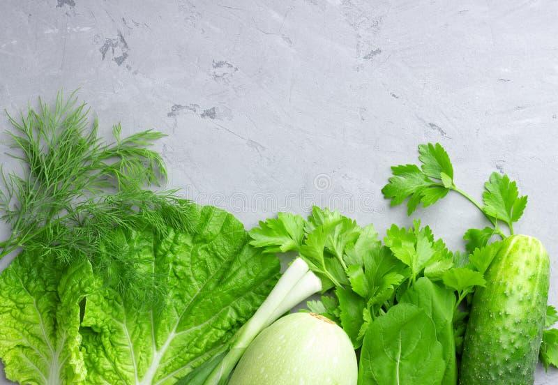 Υπόβαθρο με τα πράσινα λαχανικά, τη σαλάτα, το αγγούρι, το πράσινα κρεμμύδι και τα κολοκύθια στον γκρίζο πίνακα πετρών στοκ φωτογραφία με δικαίωμα ελεύθερης χρήσης