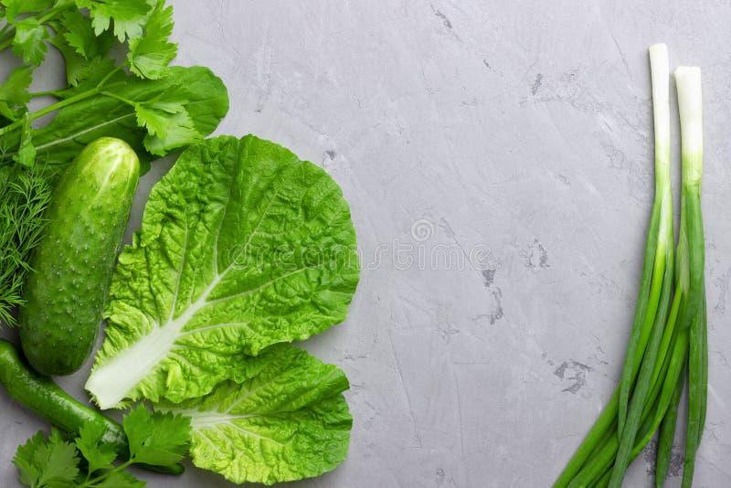 Υπόβαθρο με τα πράσινα λαχανικά, τη σαλάτα, το αγγούρι, το πράσινα κρεμμύδι και τα κολοκύθια στην γκρίζα επιτραπέζια κορυφή πετρώ στοκ εικόνες