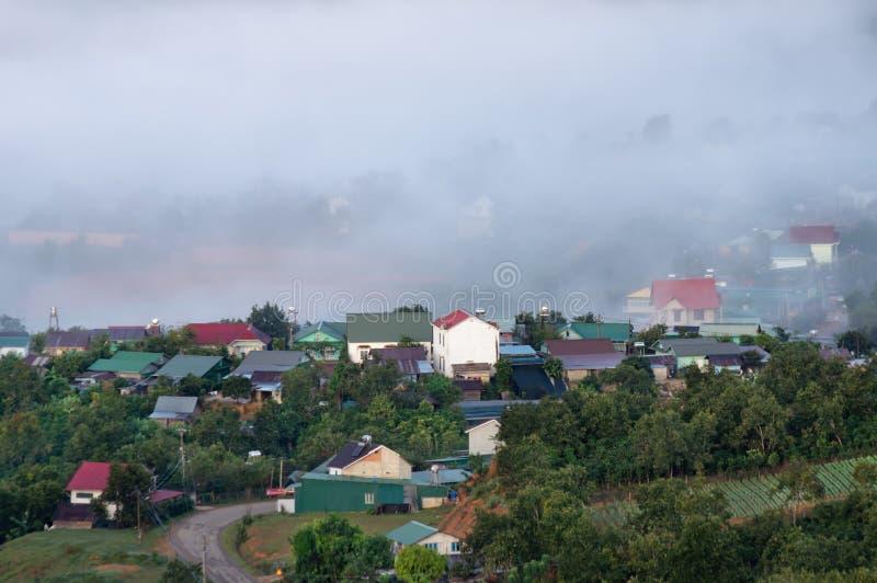 Υπόβαθρο με την πυκνή ομίχλη και μαγικό φως στην ανατολή Το αγρόκτημα καφέ και τα μικρά σπίτια στο λαμπρό μέρος 8 ηλιοφάνειας στοκ φωτογραφία με δικαίωμα ελεύθερης χρήσης