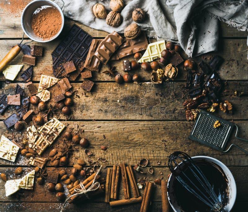 Υπόβαθρο με τη σοκολάτα, τα καρύδια και τα καρυκεύματα πέρα από το ξύλινο σκηνικό στοκ εικόνες