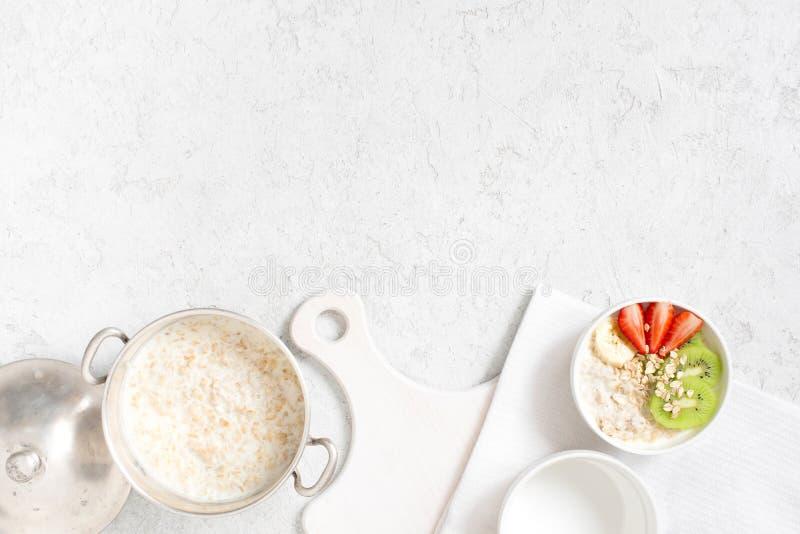 Υπόβαθρο με oatmeal το κουάκερ και νωποί καρποί στον άσπρο πίνακα στοκ εικόνες