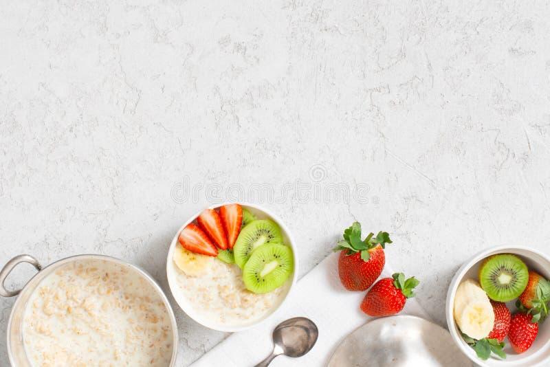 Υπόβαθρο με oatmeal το κουάκερ και νωποί καρποί στον άσπρο πίνακα στοκ φωτογραφία με δικαίωμα ελεύθερης χρήσης