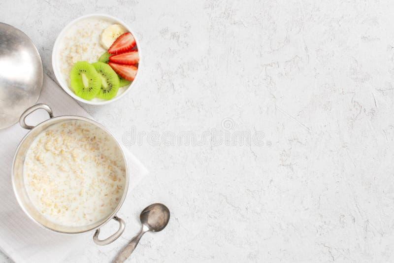 Υπόβαθρο με oatmeal το κουάκερ και νωποί καρποί στον άσπρο πίνακα στοκ εικόνα με δικαίωμα ελεύθερης χρήσης