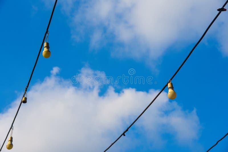Υπόβαθρο μπλε ουρανού με τα σύννεφα στη Μπανγκόκ στην Ταϊλάνδη μακριά ηλεκτρική γιρλάντα ΝΕ για το φωτισμό με τις άσπρες λάμπες φ στοκ εικόνες με δικαίωμα ελεύθερης χρήσης
