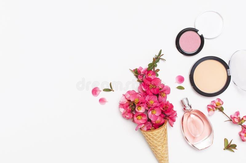 Υπόβαθρο ομορφιάς Ο κώνος βαφλών με το ρόδινο ελατήριο ανθίζει και διαφορετικό καλλυντικό makeup στο ελαφρύ υπόβαθρο Κραγιόν σκον στοκ εικόνα με δικαίωμα ελεύθερης χρήσης