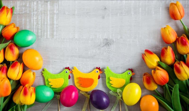 Υπόβαθρο Πάσχας - κλείστε επάνω των ζωηρόχρωμων αυγών, των διακοσμητικών νεοσσών και των τουλιπών πέρα από τον ξύλινο πίνακα στοκ εικόνα
