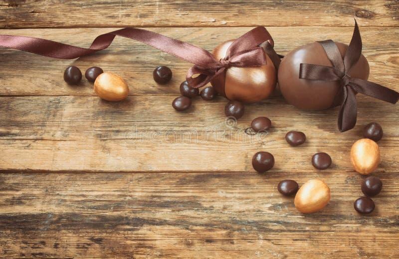 Υπόβαθρο Πάσχας με ένα αυγό χρυσού και σοκολάτας, καραμέλα, πλευρό μεταξιού στοκ εικόνες