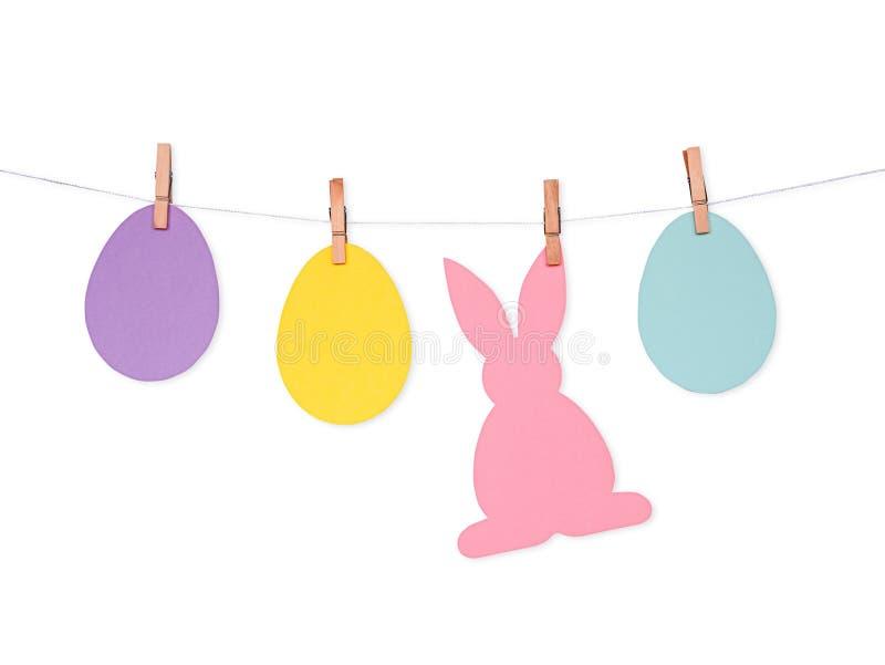 Υπόβαθρο Πάσχας με τα ζωηρόχρωμα αυγά εγγράφου και κουνέλι στο σχοινί στοκ εικόνα