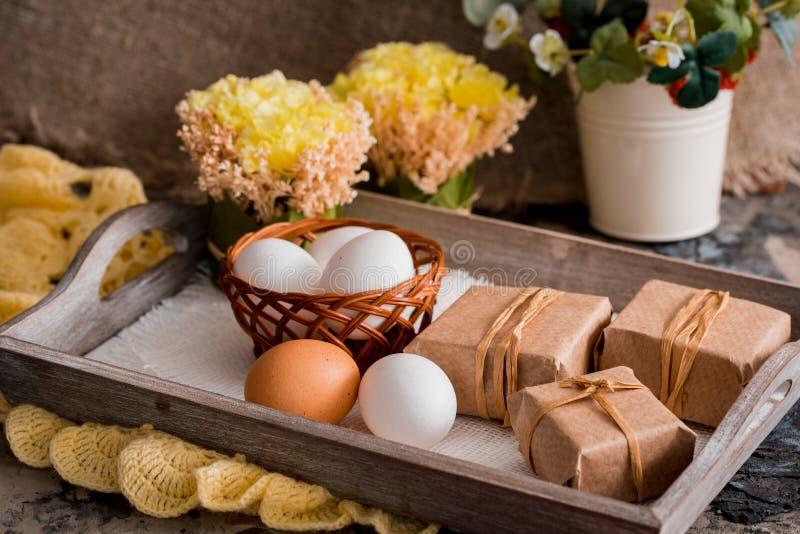Υπόβαθρο Πάσχας με τα ζωηρόχρωμα αυγά και τις κίτρινες τουλίπες πέρα από το άσπρο ξύλο στοκ εικόνες με δικαίωμα ελεύθερης χρήσης
