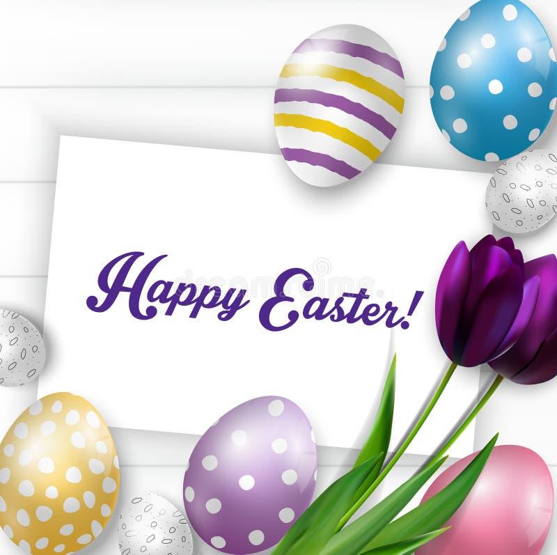 Υπόβαθρο Πάσχας με τα ζωηρόχρωμα αυγά, τις πορφυρές τουλίπες και τη ευχετήρια κάρτα πέρα από το άσπρο ξύλο απεικόνιση αποθεμάτων