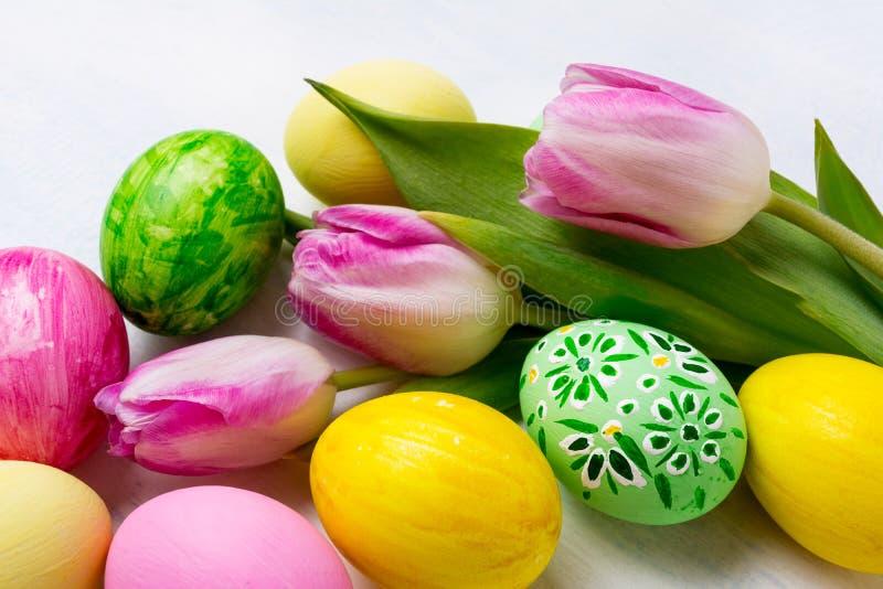 Υπόβαθρο Πάσχας με τα πράσινα, κίτρινα, ρόδινα χρωματισμένα αυγά στο ν στοκ εικόνες