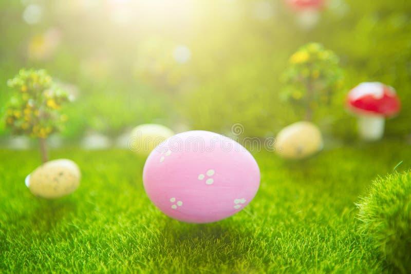 Υπόβαθρο Πάσχας με τα ρόδινα αυγά Πάσχας στην πράσινη χλόη στα χρώματα κρητιδογραφιών την άνοιξη του κόσμου Dreamland ή νεράιδων στοκ εικόνες