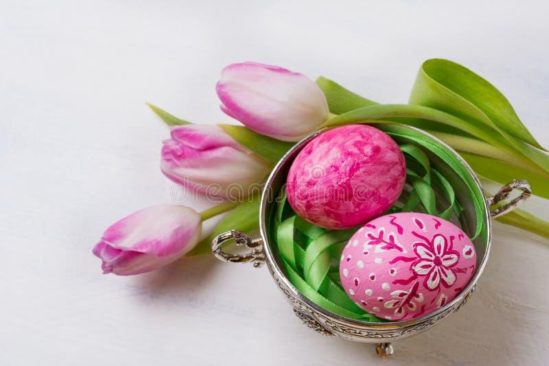 Υπόβαθρο Πάσχας με τα ρόδινα αυγά στο κύπελλο μετάλλων στοκ εικόνα με δικαίωμα ελεύθερης χρήσης