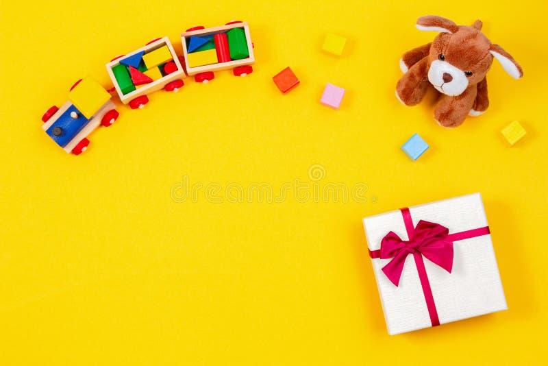 Υπόβαθρο παιχνιδιών μωρών παιδιών Ξύλινο τραίνο, γεμισμένο κουτάβι και παρόν κιβώτιο δώρων στο κίτρινο υπόβαθρο στοκ εικόνες