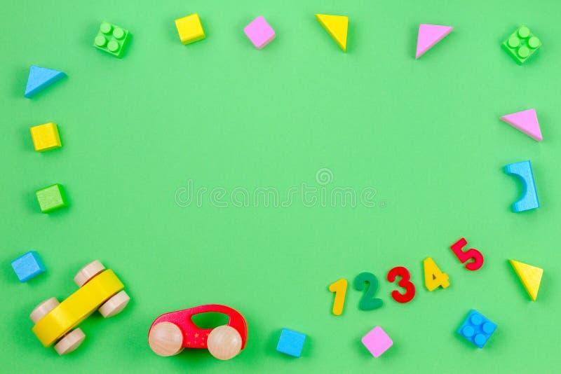 Υπόβαθρο παιχνιδιών παιδιών μωρών Ζωηρόχρωμα ξύλινα κύβοι, αυτοκίνητα και αριθμοί στο πράσινο υπόβαθρο στοκ φωτογραφία με δικαίωμα ελεύθερης χρήσης